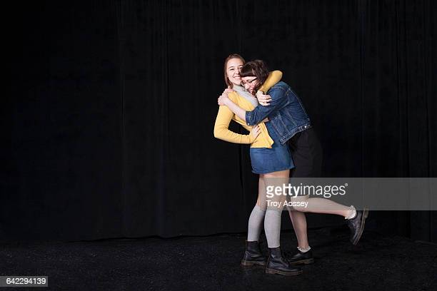 two girls hugging against black backdrop. - only teenage girls stock pictures, royalty-free photos & images