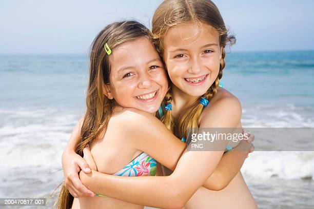Two girls (9-11) hugging on beach, portrait