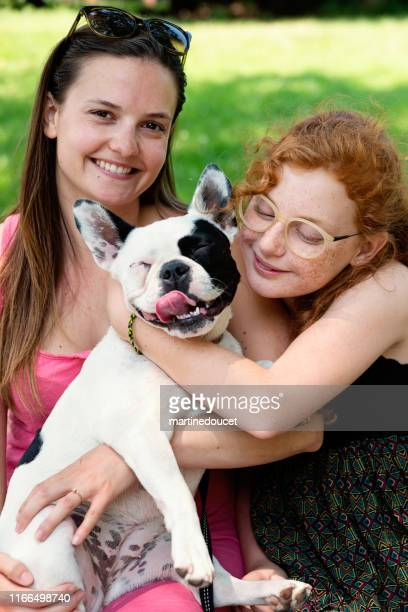 """two girls in a park with a dog - """"martine doucet"""" or martinedoucet stock pictures, royalty-free photos & images"""