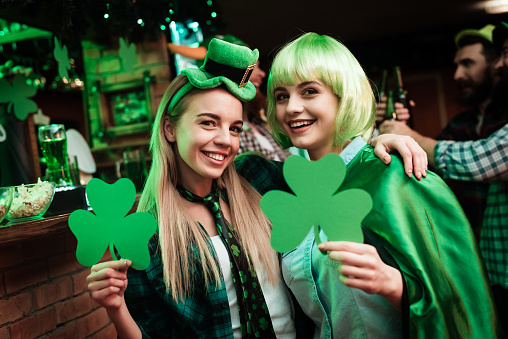 Two girls in a wig and a cap are photographed in a bar. 905927622