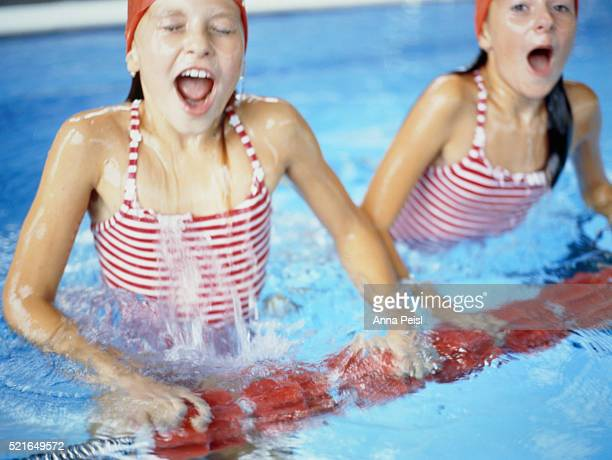 Two girls in an indoor swimming pool