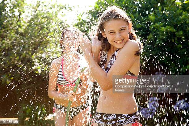 two girls in bathing suits playing with water hose