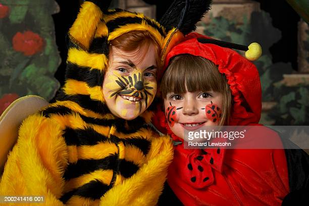 two girls (6-8) in bee and ladybird costumes, smiling, portrait - school play stock photos and pictures