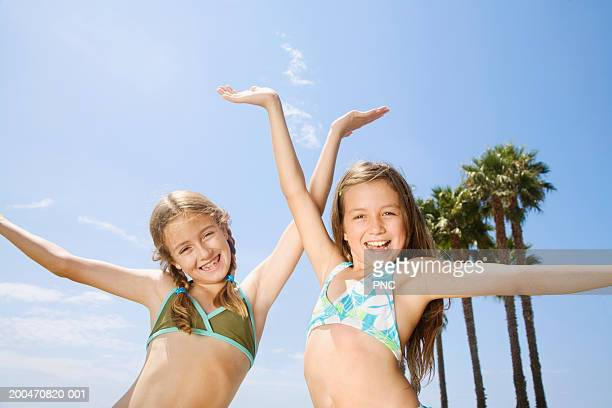 Two girls (9-11) in bikinis, arms raised, portrait, low angle view