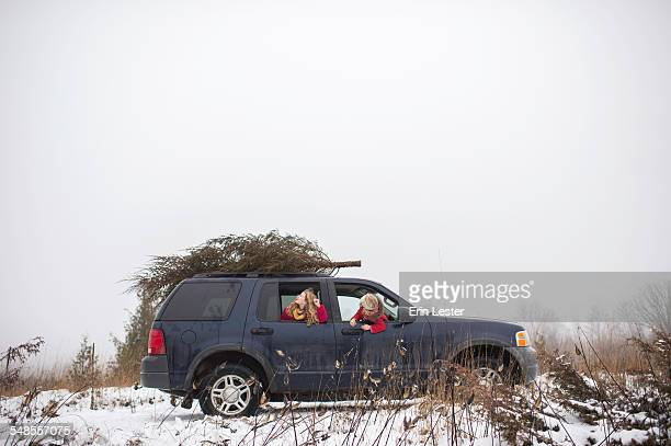 Two girls in car with christmas tree on roof