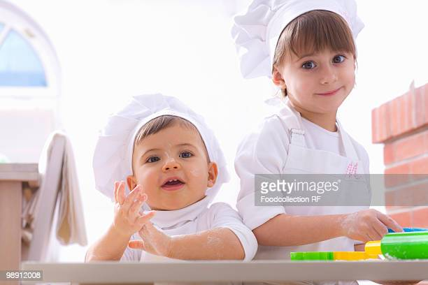 Two girls (1-5) in chef's uniform baking, smiling, close-up