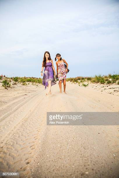 two girls in colorful dresses walking on a sandy beach - wantagh stock pictures, royalty-free photos & images