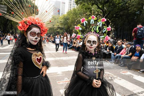 Two girls in costume seen during the Catrina Festival Thousands of people took to the streets of Mexico City to watch the procession of Catrinas...