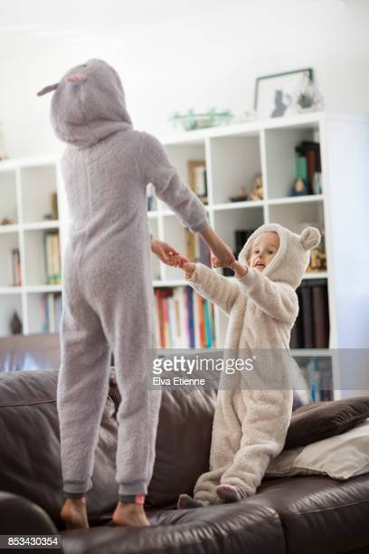 Two girls in cozy hooded pyjamas, jumping on a sofa