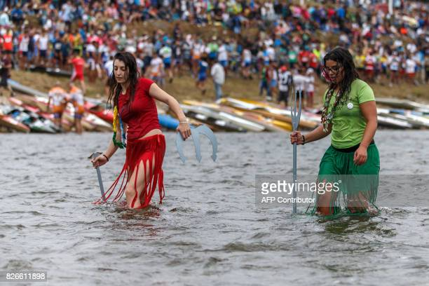 "Two girls in disguise carrying tridents walk in the river before the start of the 81th edition of the ""Descenso Internacional del Rio Sella 2017"" a..."