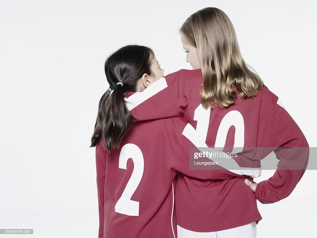 Two girls (8-11) in football strips, arms around each other, rear view : Bildbanksbilder