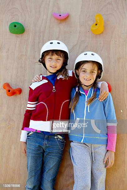 Two girls in front of a climbing wall