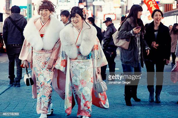 """Two girls in kimono walking through a shopping street in Shibuya during the """"Coming of Age"""" day in Japan."""