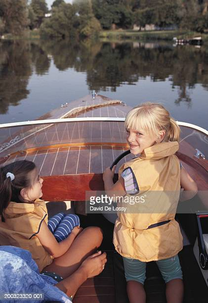two girls (6-7) in motorboat, looking over shoulder - bang boat stock pictures, royalty-free photos & images