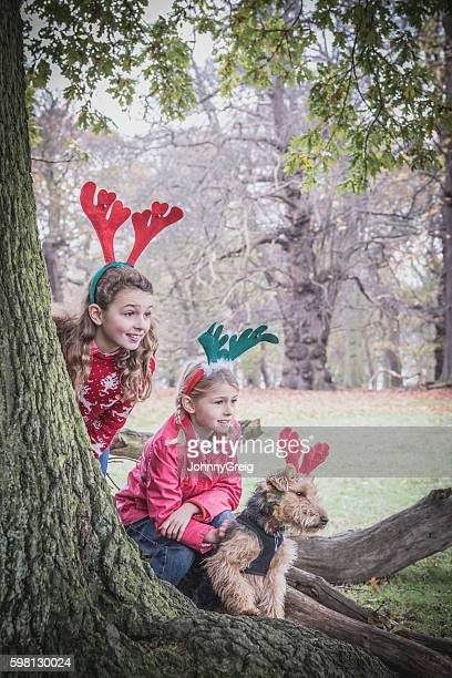 Two girls in park with reindeer antlers on heads