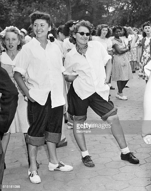 Two girls in rolledup dungarees and sloppy white shirts turn up for a dance on the mall in Central Park in 1946 As the 1950s rolled in the look...