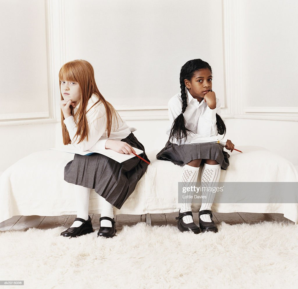 Two Girls in School Uniform Sitting on Bed and Looking Displeased : Stock Photo