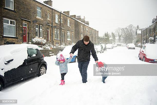 Two girls in snow with their father