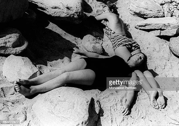 Two girls in swimsuit sunbathing lying on the sand. August 1943