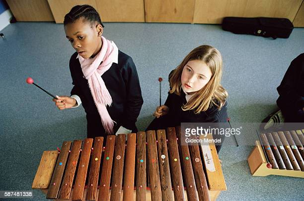 Two girls in the Millfields Community School pause for a moment during their break time orchestra rehearsal This is a large innercity primary school...