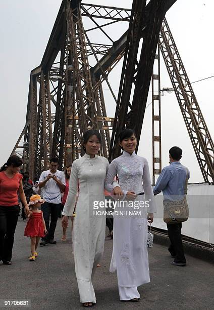 Two girls in traditional 'ao dai' dress walk across the Frenchbuilt 107yearold Long Bien bridge formerly named Paul Doumer after the name of a French...