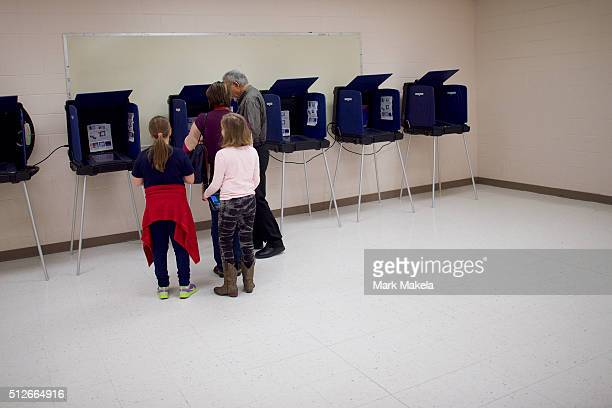 Two girls join their mother to vote at the Polo Park polling precinct for the South Carolina Democratic Presidential Primary February 27 2016 in...
