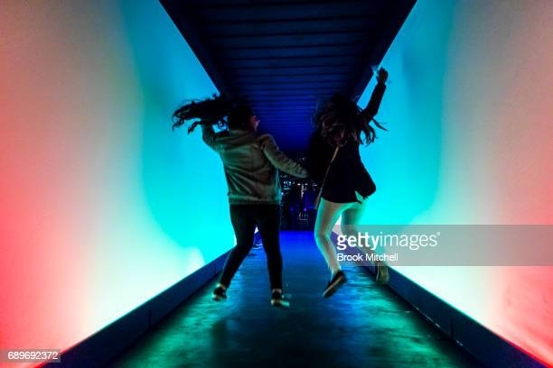 Two girls jump inside the Chromesthesia light installation on May 29 2017 in Sydney Australia Vivid Sydney is an annual festival that features light...