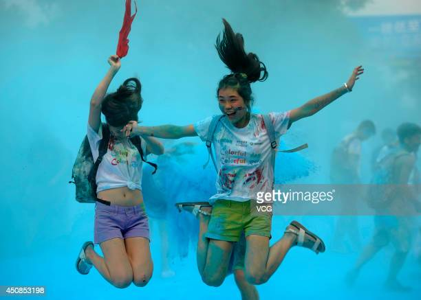 Two girls jump into the air covered with blue powder on June 18 2014 in Changsha Hunan province of China A color run was held in china's southeast...