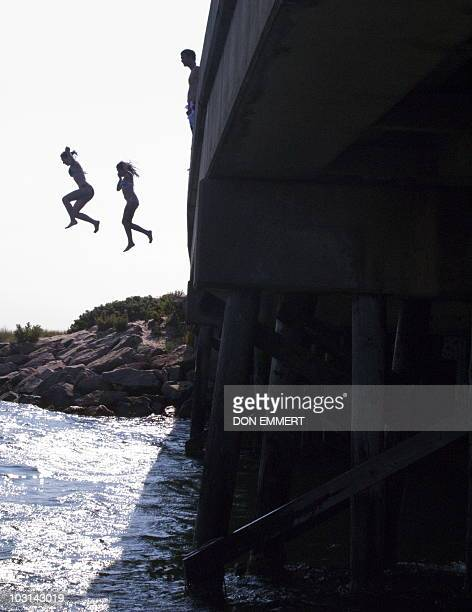Two girls jump off a bridge into the waters of the Vineyard Sound July 28 2010 in Falmouth Massachusetts Falmouth is located in the southwestern part...