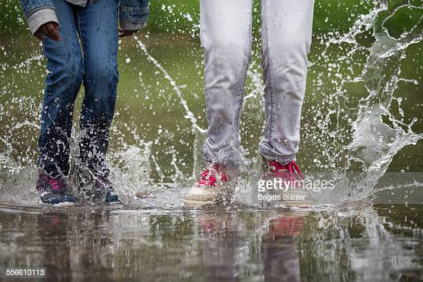 two girls jumping in water. - wet jeans stock photos and pictures