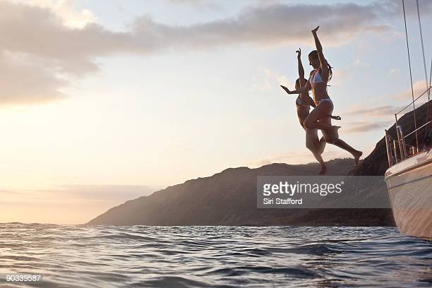 Two girls jumping off of boat