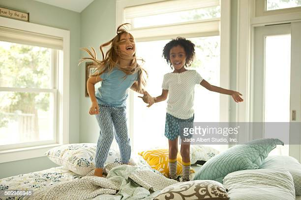 two girls jumping on bed together - slumber party stock pictures, royalty-free photos & images