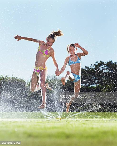 Two girls (9-12) jumping over sprinkler, holding hands