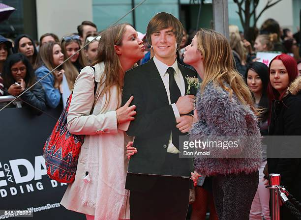 Two girls kiss a Zac Efron poster during the Mike And Dave Need Wedding Dates fan premiere at Event Cinemas Parramatta on July 6 2016 in Sydney...