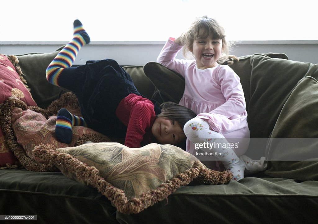 Two girls (3-4) laughing and playing on sofa : Foto stock