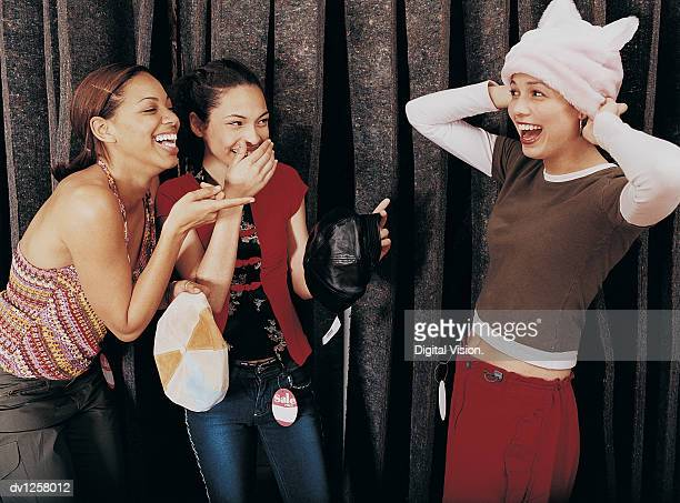 Two Girls Laughing at a Young Girl Trying on a Hat in the Changing Room of a Clothes Shop