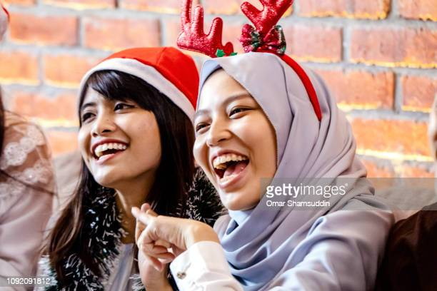 Two girls laughing during Christmas gathering with friends