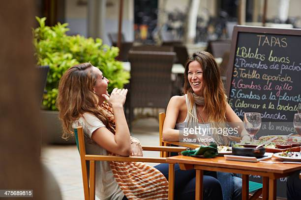 two girls laughing together at restaurant - klaus vedfelt mallorca stock pictures, royalty-free photos & images