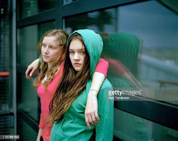 Two Girls Leaning Against a Window