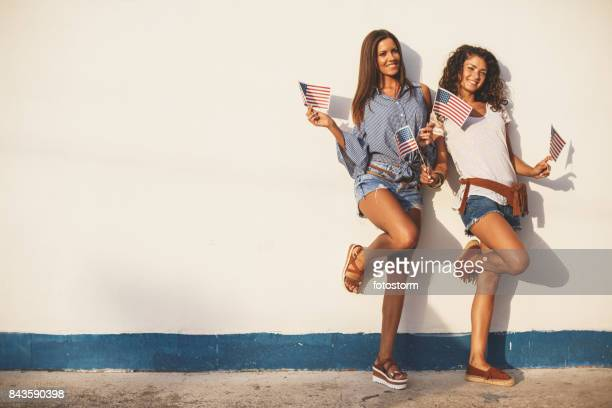 two girls leaning on a wall - fourth of july stock pictures, royalty-free photos & images
