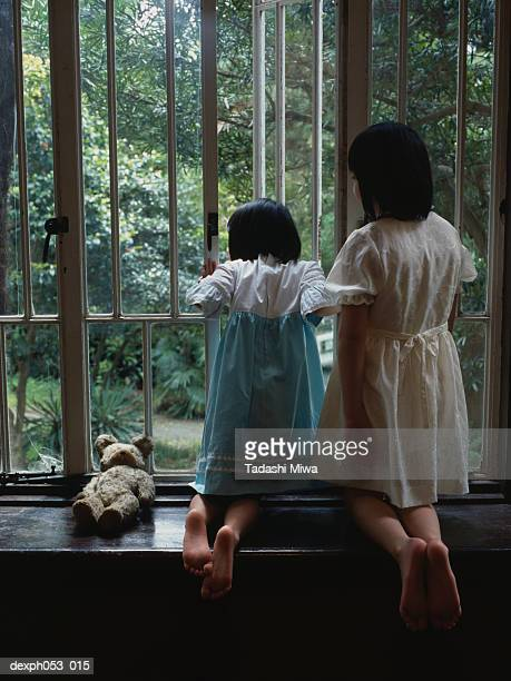 Two girls leaning on sill, looking out window, rear view