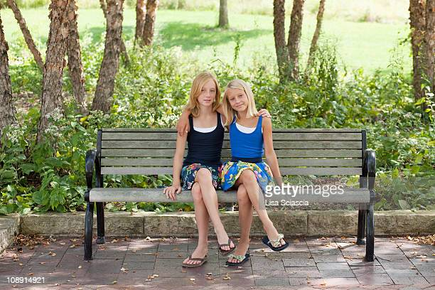 Two Girls legs crossed on a bench