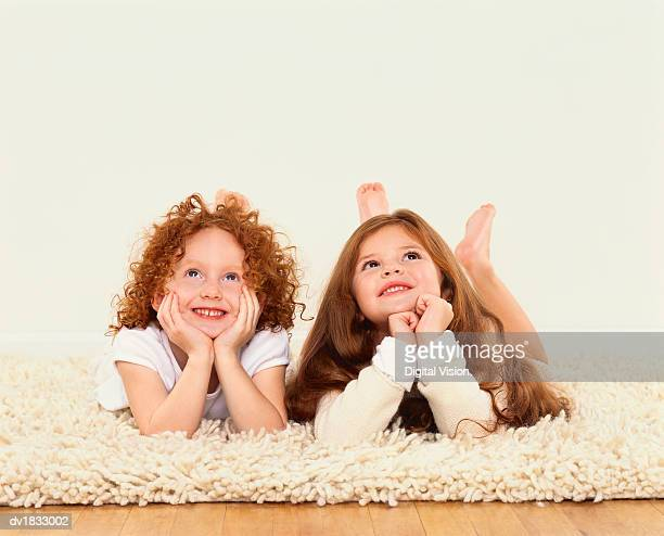 Two Girls Lie on a Rug Leaning on Their Elbows and Looking Up
