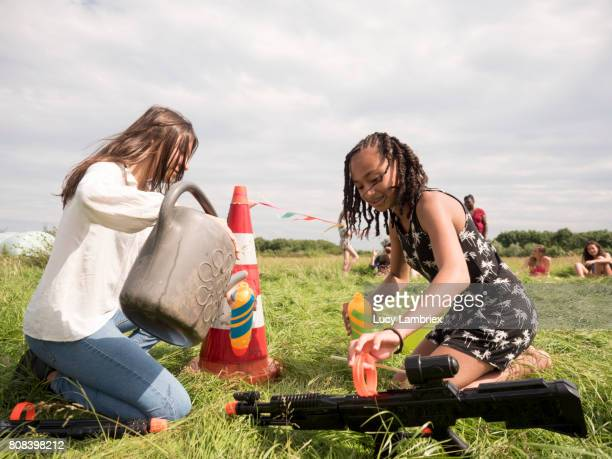 Two girls loading their water rifles