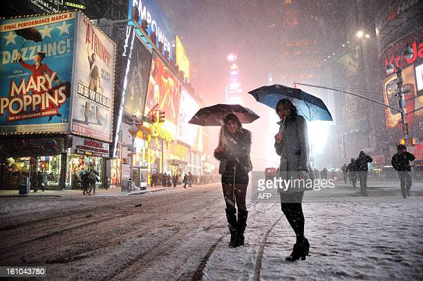 Two girls look for a taxi in the snow in Times Square in New York on February 8 2013 during a storm affecting the northeast US The storm was forecast...