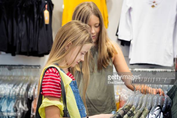 two girls looking at clothes in a store in germany - indipendenza foto e immagini stock