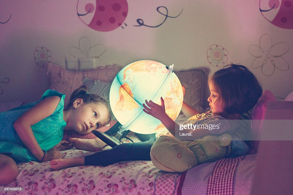 Two girls (2-3, 6-7) looking at illuminated lamp in shape of globe : Stock Photo