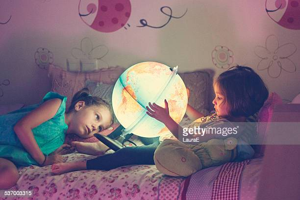 Two girls (2-3, 6-7) looking at illuminated lamp in shape of globe