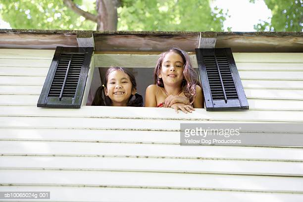 Two girls (8-9) looking out of treehouse window, portrait, low angle view