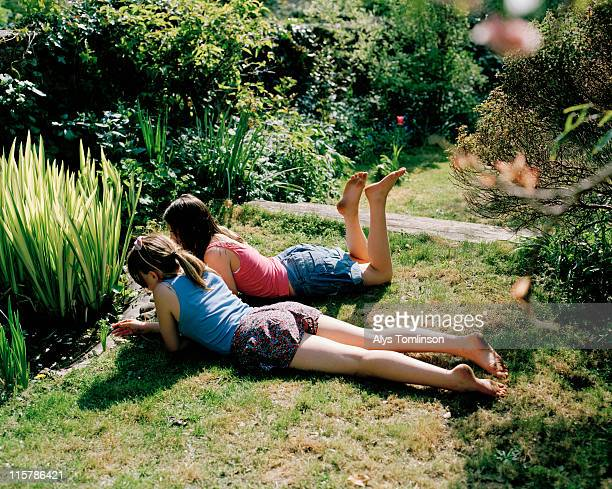 two girls lying down in a garden - barefoot feet up lying down girl stock photos and pictures